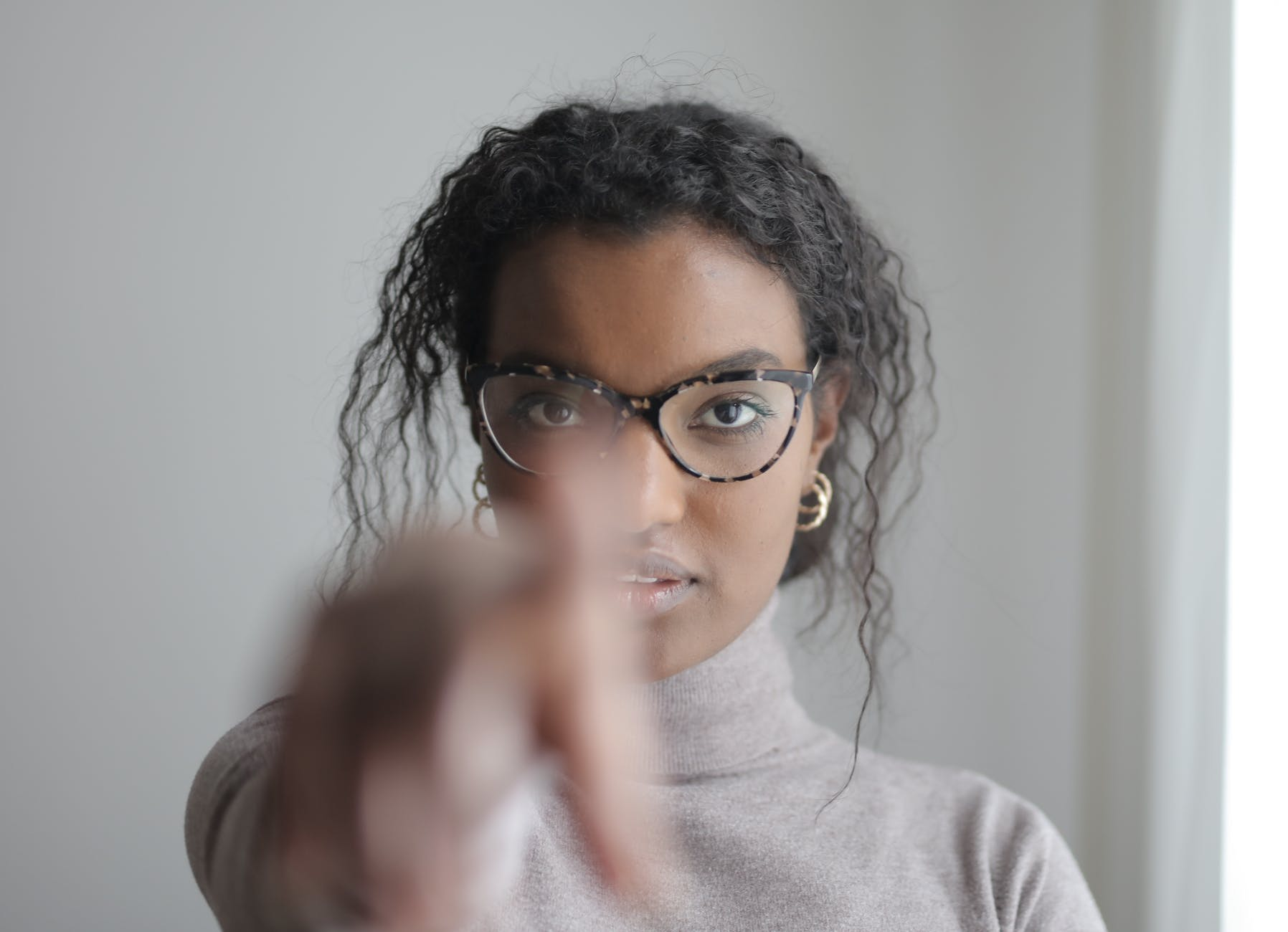 young ethnic woman pointing at camera
