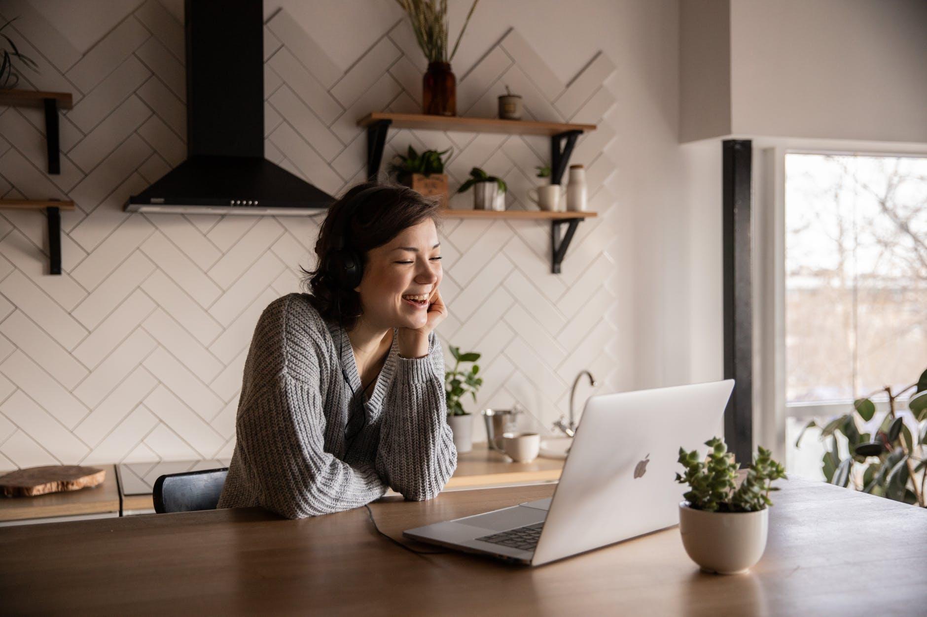 smiling woman talking via laptop in kitchen